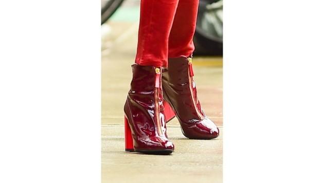 Yolanda Hadid trägt glänzend rote Lack-Stiefeletten zur roten Lederhosen.