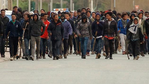 Mit Stöcken bewaffnete afrikanische Migranten in den Straßen von Calais (Bild: Associated Press)