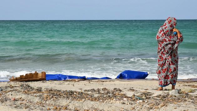 Eine Libyerin begutachtet die Reste eines in Küstennähe gekenterten Schlauchboots (Archivbild). (Bild: APA/AFP/STRINGER)