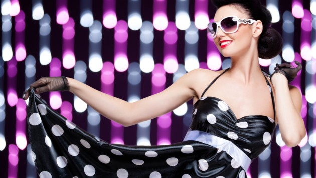 young beautiful caucasian woman posing, retro styling, over abstract lights