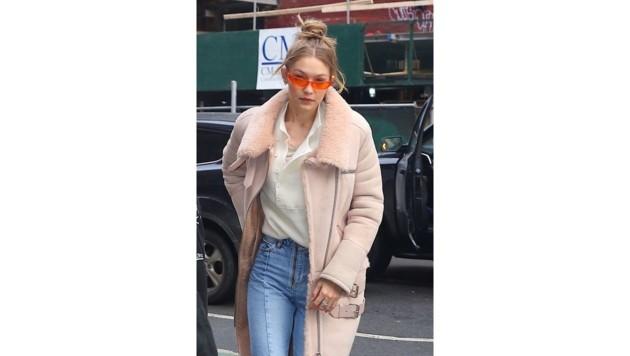 Gigi Hadid peppt ihr Outfit mit einer orangefarbigen Brille auf.