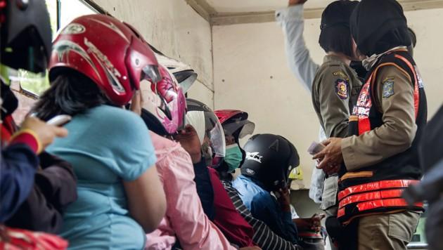 Die Paare wurden in Helmen von der Polizei abgeführt. (Bild: AFP)