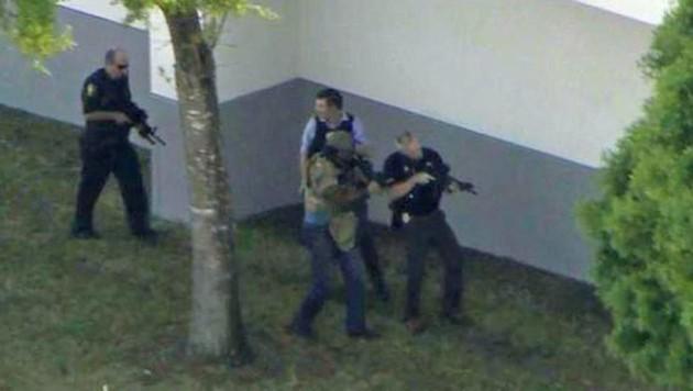 Einsatzkräfte durchkämmen das Schulgelände.