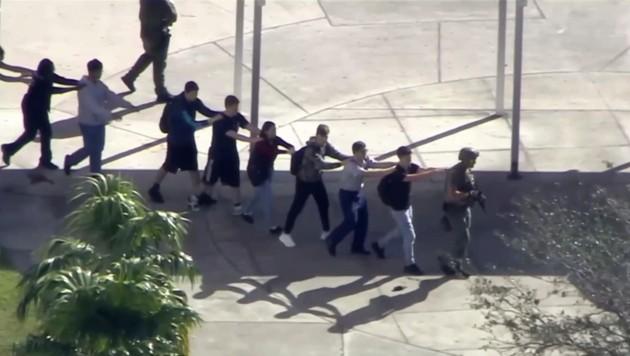 Schüler werden von einem schwer bewaffneten Polizisten aus dem Gebäude geführt.