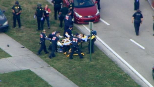 Verletzte werden auf Tragen weggebracht.