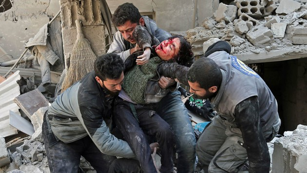 Helfer bergen ein verletztes Kind nach einem Bombardement in der Stadt Hamouria in der Region Ost-Ghouta. (Bild: AFP)