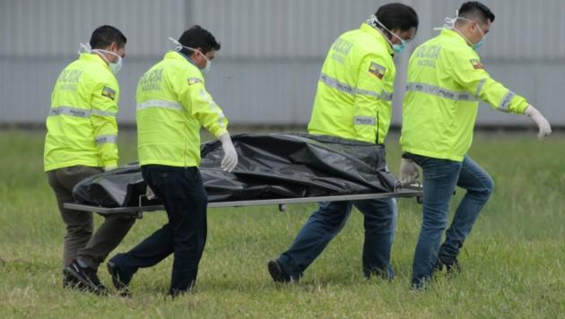 Ecuadorianische Einsatzkräfte beim Abtransport der Leiche eines blinden Passagiers