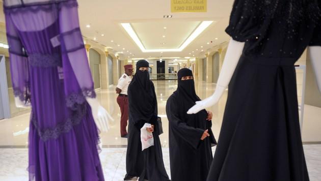 Nahezu gänzlich verschleierte Kundinnen begutachten in einem saudischen Kaufhaus weitaus freizügigere Mode.