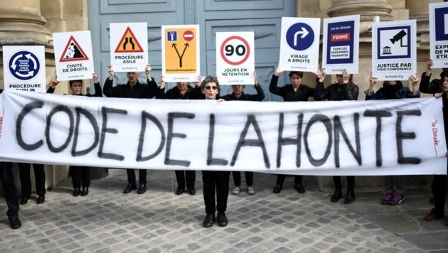 """Menschen demonstrieren in Paris gegen die schärferen Asylgesetze. Auf dem Plakat steht: """"Gesetz der Schande"""". (Bild: AFP )"""