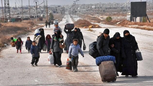 Syrische Flüchtlinge mit ihrem wenigen Hab und Gut (Bild: AFP)