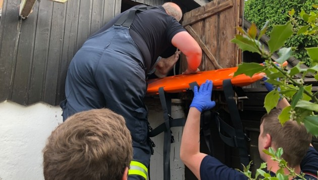 Feuerwehrleute bergen den verletzten Patienten mit einem Rettungsbrett aus der Dachluke. (Bild: FF Traun)