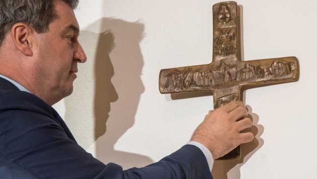 Der bayrische Ministerpräsident Markus Söder (CSU) hängt ein Kreuz in der bayrischen Staatskanzlei in München auf. (Bild: AFP)