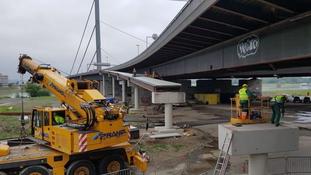An der Linzer Voest-Brücke wird derzeit ein neuer Radler- und Fußgehersteg errichtet. Dass er schon angeröstet ist, stört manchen Baustellen-Kiebitz. Der Rost ist aber egal, das Bauwerk ist ohnehin nur provisorisch und steht bloß zwei Jahre. (Bild: Werner Pöchinger)