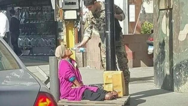 Foto vom März dieses Jahres: Ein Soldat teilt sein Wasser mit der schwerbehinderten Bettlerin. Was zu diesem Zeitpunkt niemand wusste: Sie hatte fast eine Million Euro auf ihrem Bankkonto. (Bild: Action Press)