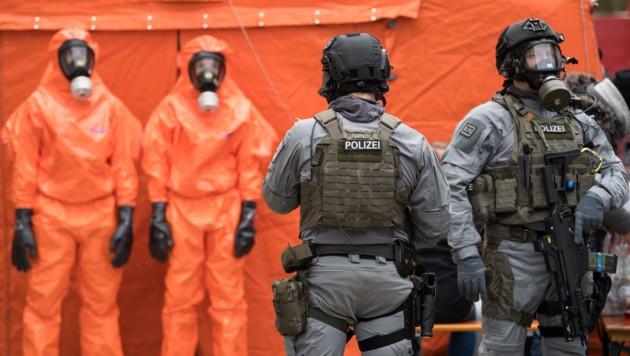 Schwer bewaffnete Polizisten mit Atemschutzmasken (Bild: APA/dpa/Bernd von Jutrczenka)