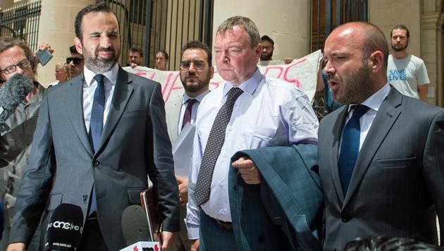 Lifeline-Kapitän Claus-Peter Reisch (Mitte) weist die gegen ihn erhobenen Anschuldigungen zurück. Er will lediglich Leben gerettet haben. (Bild: AP)