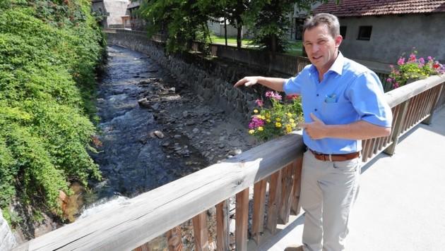 Bürgermeister Johann Schmidhofer (VP) zeigt, wie hoch das Wasser dieses Bachs vor einem Jahr stand. (Bild: Juergen Radspieler)