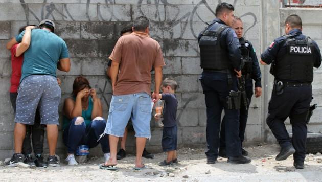 Die Leichen wurden in einem Haus in Ciudad Juarez gefunden. Im Bild: Polizisten und verzweifelte Angehörige der Toten am Tatort. (Bild: APA/AFP/HERIKA MARTINEZ)