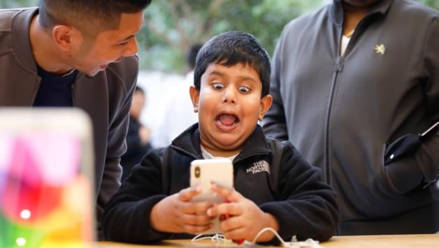 Verkaufsstart des iPhone X: Ein Bub schneidet Grimassen, um das neue animierte Emoji-Feature auszuprobieren. (Bild: APA/AFP/Elijah Nouvelage)