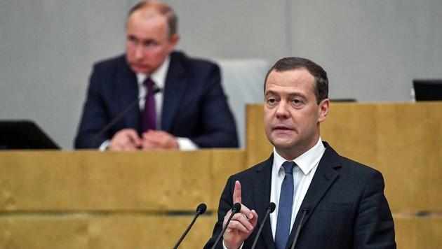 Ministerpräsident Dmitri Medwedew spricht noch im Konjunktiv, die Sanktionen gegen sein Land müssen erst durch den US-Kongress bewilligt werden. (Bild: APA/AFP/YURI KADOBNOV)