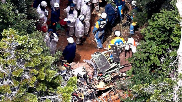 Einsatzkräfte an der Absturzstelle des Hubschraubers in einem Wald (Bild: AP/Kyodo News)