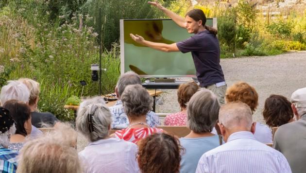 Felix Schlatti bei einem Vortrag. Die kleine Kamera neben dem Monitor nimmt die Pflanzen auf. Vortragsbesucher können sie auf diese Weise besser sehen. (Bild: RK Eberwein)