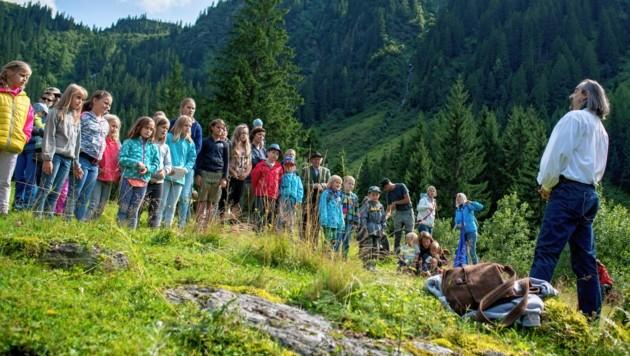 """Die prächtigen Naturschauplätze um den Grimming und im Donnersbachtal werden für vier Tag zur Freiluftbühne für fantastische Erzählungen, wie beispielsweise hier bei einer """"Geschichtenwanderung"""". (Bild: Christoph Zeiselberger)"""
