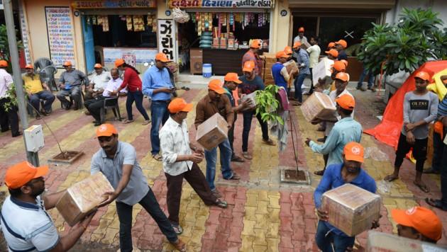 Helfer verpacken Lebensmittelpakete (Bild: AFP)