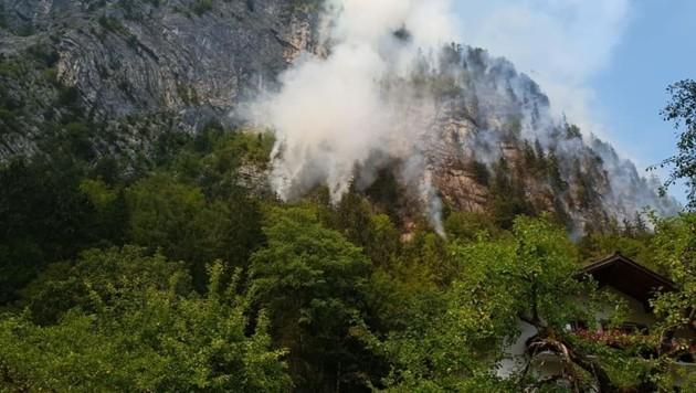 Das Feuer lodert direkt oberhalb einer Siedlung, ständig stürzen Felsen und brennende Stämme ab (Bild: FF Obertraun)