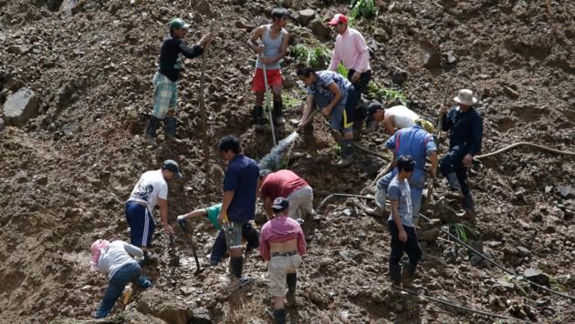 Bergbauarbeiter graben teils mit bloßen Händen nach ihren Kollegen. (Bild: AP)