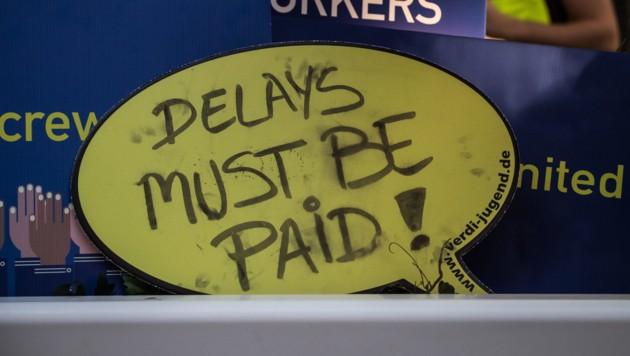 Eine gemalte Sprechblase der streikenden Ryanair-Mitarbeiter fordert eine Bezahlung der Crew - auch bei Verspätung. (Bild: APA/dpa/Andreas Arnold)