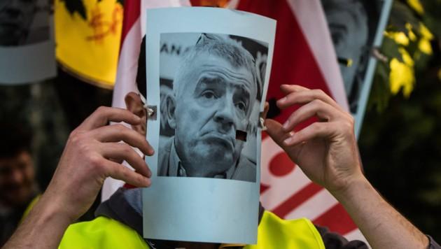 Ein streikender Flugbegleiter setzt sich eine Maske auf, die das Porträt von Michael Kevin OáLeary, Vorsitzender von Ryanair, zeigt. (Bild: APA/dpa/Andreas Arnold)