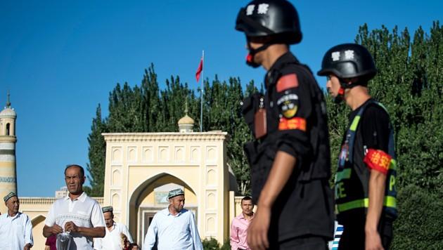 Chinesische Polizisten überwachen Uiguren nach dem Gebet in einer Moschee in der Unruheprovinz Xinjiang.