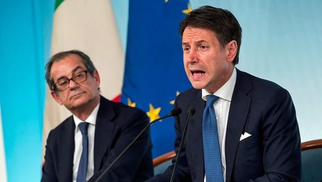 Premier Giuseppe Conte (hier im Bild mit Finanzminister Giovanni Tria) will die Wahlversprechen der Koalitionsparteien umsetzen. Dafür muss sich Italien weiter verschulden. Davor aber warnen die EU und der IWF. (Bild: AP)