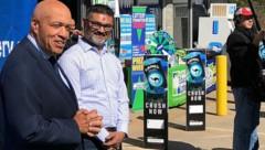Tony Cooper von der Lotteriegesellschaft mit dem Besitzer von KC Mart, CJ Patel (Bild: AP)