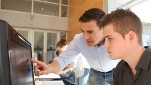 Teacher and student working on computer (Bild: goodluz - stock.adobe.com)
