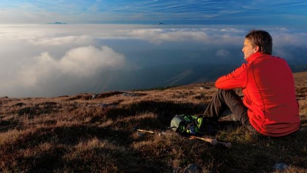 Auf den Bergen blicken viele Wanderer auf eine Nebeldecke