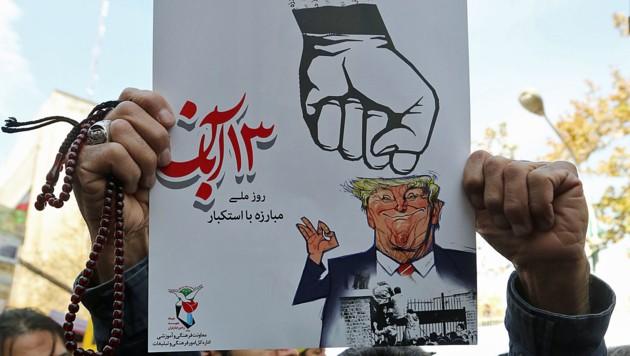 """Ein wütender Demonstrant in Teheran zeigt, mit welcher Wucht die """"iranische Faust"""" US-Präsident Donald Trump treffen wird. (Bild: APA/AFP/ATTA KENARE)"""