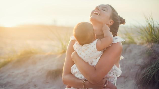 Shot of happy mother holding her baby girl on the beach. (Bild: ©abelena - stock.adobe.com)