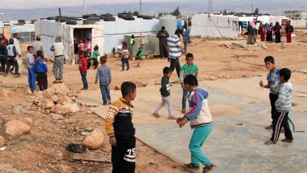 Syrische Kinder spielen Fußball in einem inoffiziellen Camp.
