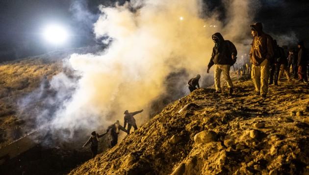Migranten laufen vor den Nebelwolken aus Tränengas davon. (Bild: AFP )
