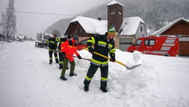 Feuerwehrleute halten vor dem Rüsthaus in Fleiß die Wege frei. (Bild: Matthias Wagner)