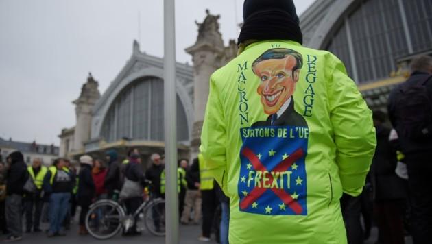 Dieser Demonstrant hätte am liebsten, wenn Präsident Macron abdankt und Frankreich die EU verlässt. (Bild: APA/AFP/GUILLAUME SOUVANT)