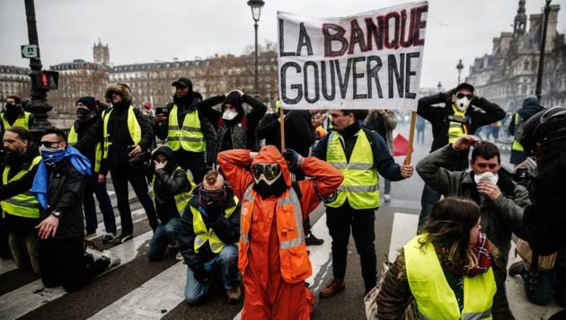 """Weil die """"Banken regieren"""", wie es auf diesem Transparent steht, wollen nun die """"Gelbwesten"""" ihren Protest auf die Finanzwelt ausweiten. (Bild: APA/AFP/Abdul ABEISSA)"""