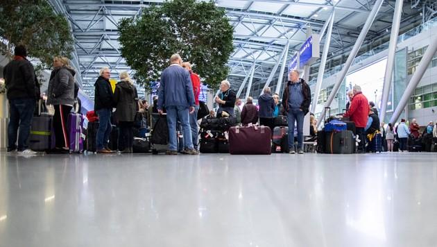 Reisende warten mit ihrem Gepäck am Flughafen Düsseldorf. (Bild: APA/dpa/Marcel Kusch)