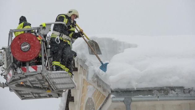Feuerwehrleute in Spital am Pyhrn beim Schneeschaufeln von einem Dach (Bild: © Jack Haijes)