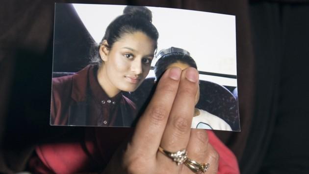 Die ältere Schwester hält ein Bild von Shamima Begum in der Hand. Die junge Britin war 2015 zum IS nach Syrien ausgereist und will jetzt wieder in ihre Heimat zurück. (Bild: AFP)