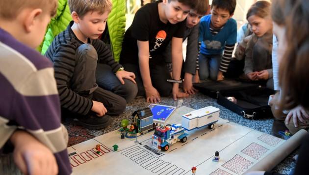 """Schulkinder mit einem Lego-Modell eines Lkw mit Abbiegeassistent im Rahmen der Übergabe der Petition """"Verpflichtende Abbiegeassistenten für Lkw"""" (Bild: APA/ROLAND SCHLAGER)"""