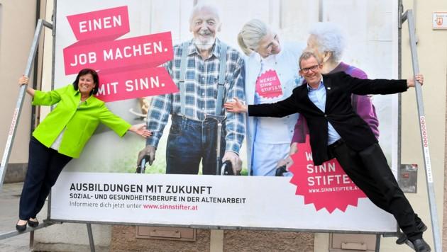 Auch ein ernstes Thema wie die Altenpflege verträgt Humor: Landesrätin Birgit Gerstorfer und Sozialer Netzwerker Martin König enthüllen die Sinnstifter-Plakatkampagne. (Bild: © Harald Dostal)