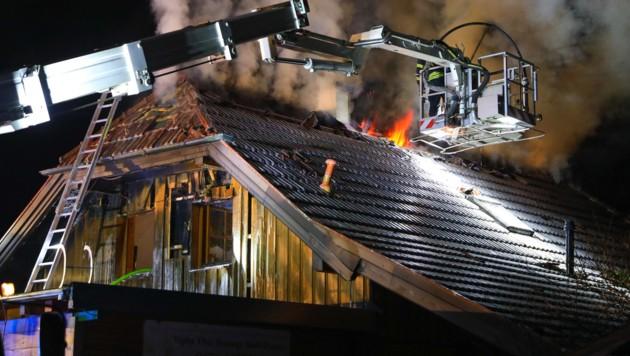 Aus dem Dach des Holzhauses schlugen den Einsatzkräften Flammen entgegen. (Bild: laumat.at/Matthias Lauber)